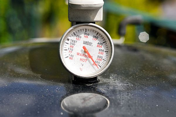 A thermometer on top of a grill.