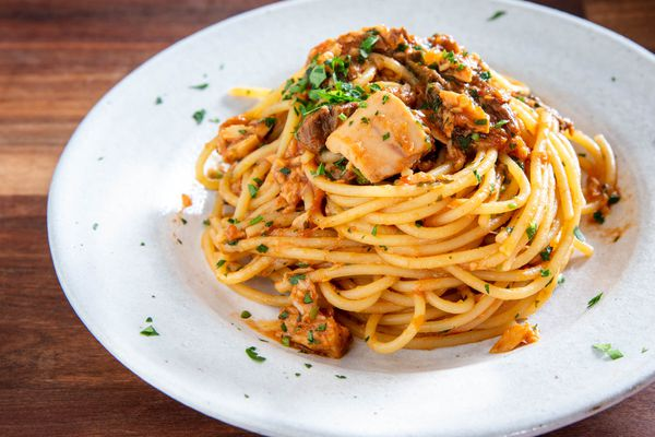 Roman-style spaghetti alla carrettiera, with tomatoes, tuna, porcini mushrooms, and more, piled on a plate and sprinkled with fresh parsley
