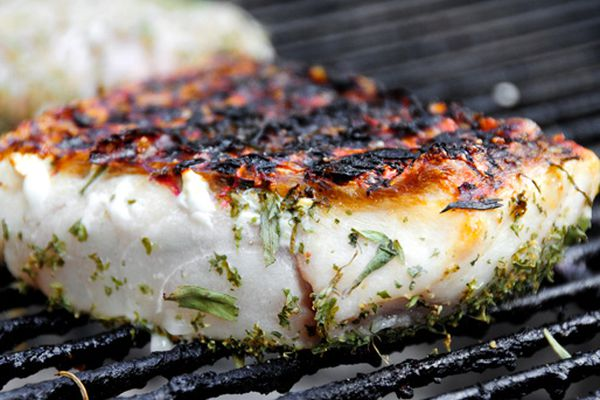 SeafoodA fish fillet seasoned with herbs being cooked on the grill.