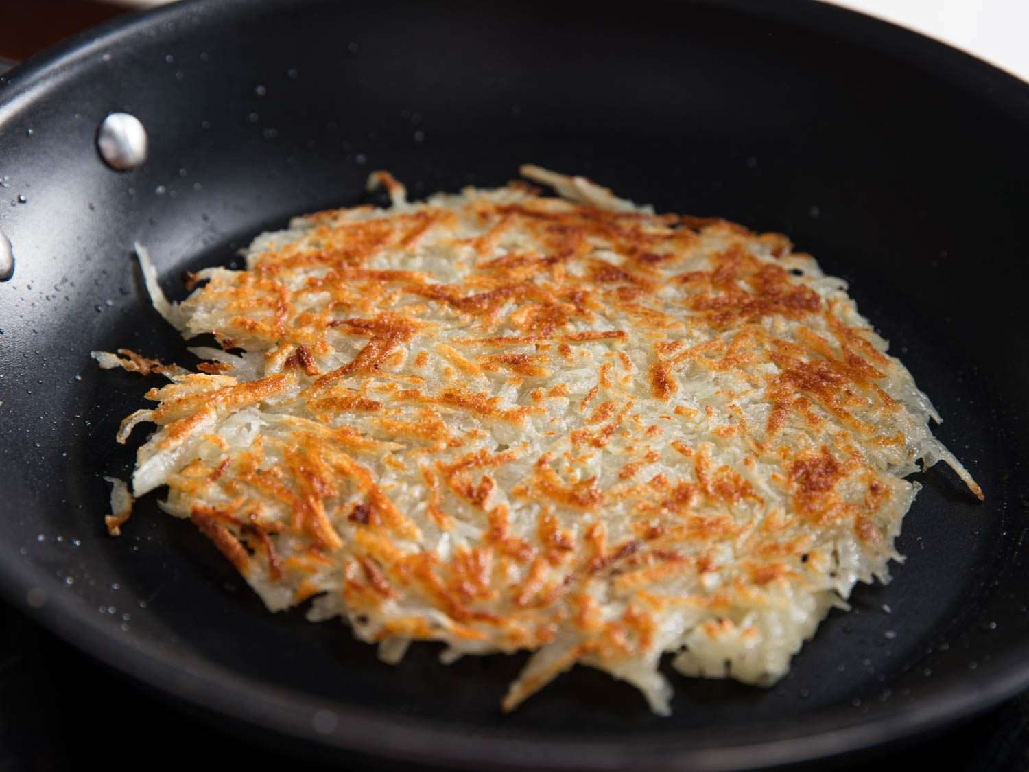 A golden disk of hash browns in a skillet