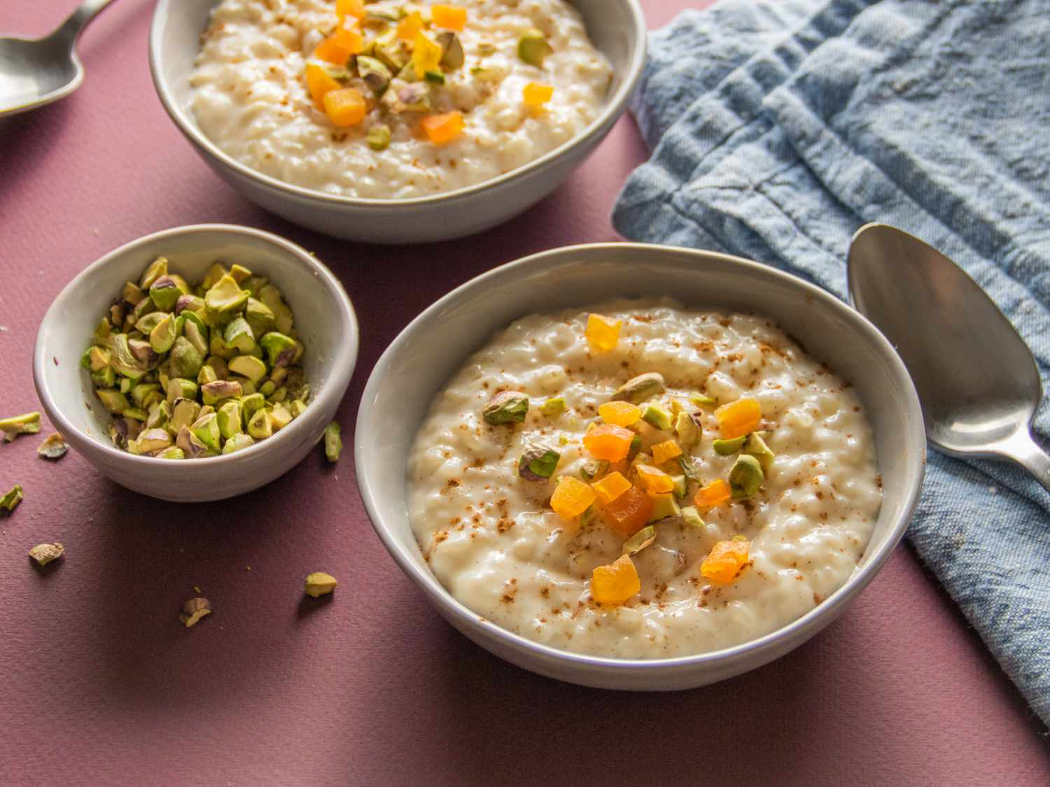 side angle of rice pudding in bowls topped with dried apricot and pistachios