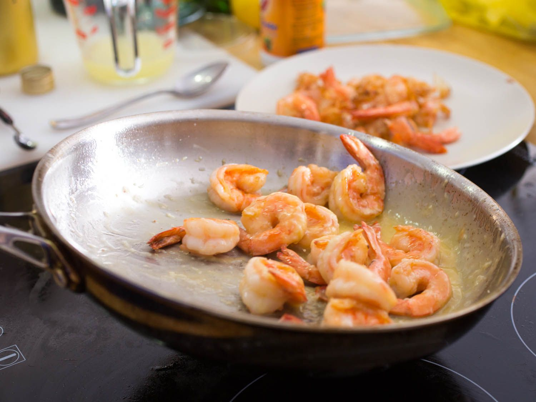 Shrimp being sautéed in butter in a pan for shrimp scampi