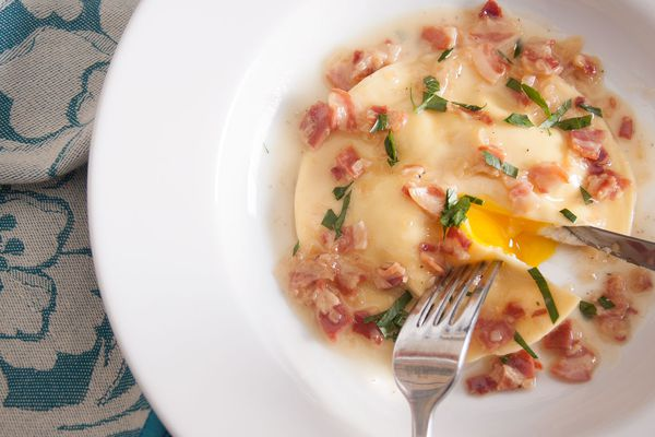 A fork and knife cutting into a single uovo in raviolo-an egg yolk inside a ravioli-that's topped with a pan sauce of parsley and pancetta.