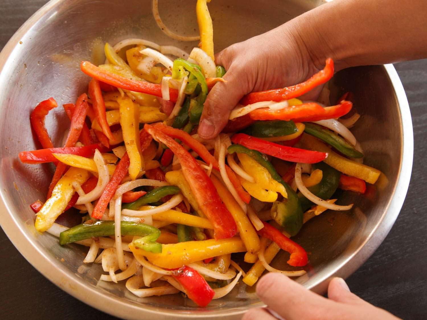 Hands tossing strips of onion and green, yellow, and red bell pepper in a metal bowl for fajitas.