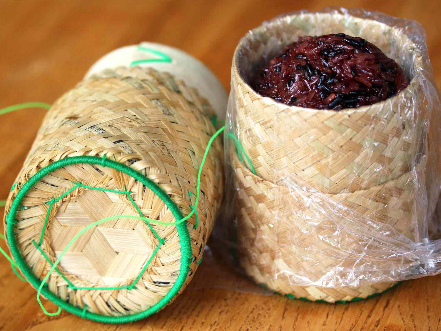 A woven basket (thip khao) with a cover, holding a mound of dark grains of sticky rice (khao niew)