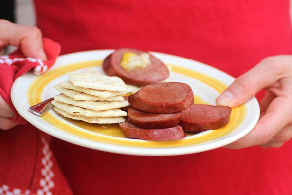 Someone holding a platter with Midwestern bologna and crackers.