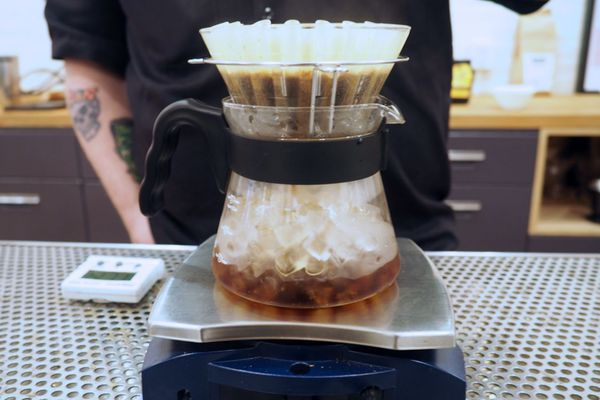Iced coffee made in the Japanese style by brewing over a carafe of ice on a sacle.