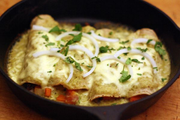 A skillet of enchiladas suizas stuffed with vegetables and topped with sliced onion and cilantro.