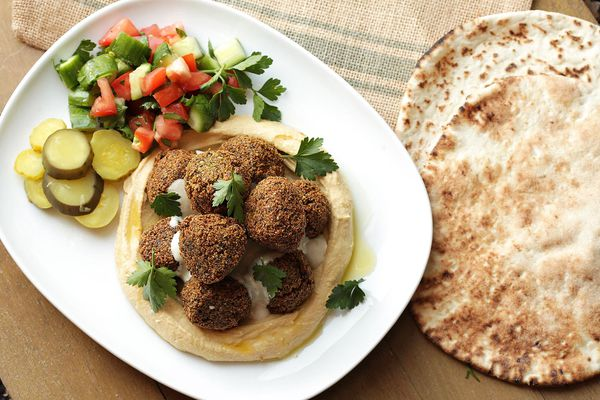 A platter of falafel garnished with flat-leaf parsley, stacked on top of hummus with pickles and cucumber-tomato salad.