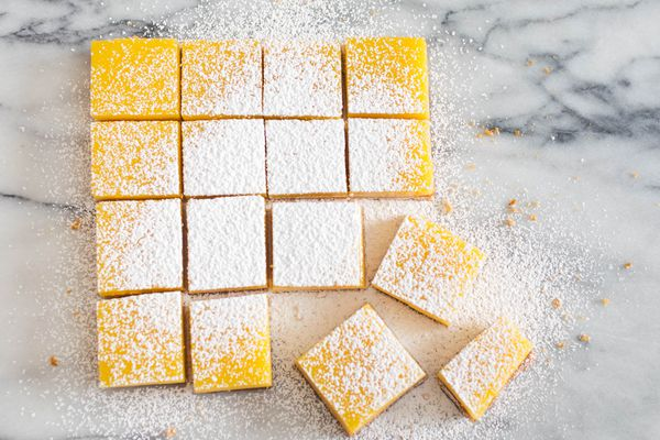 Overhead image showing sliced lemon bar squares topped with powdered sugar on a marble countertop.