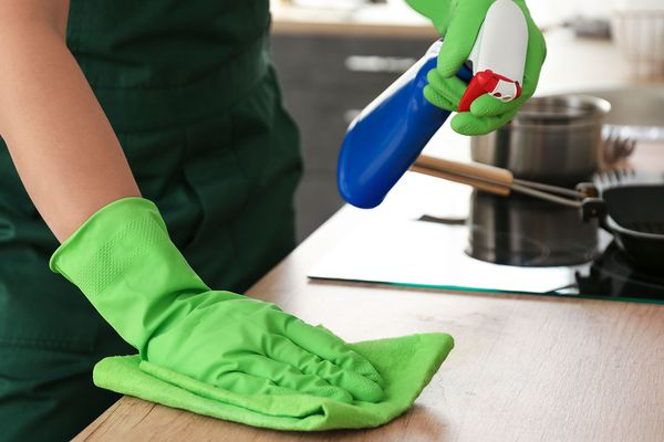 Person cleaning a kitchen counter