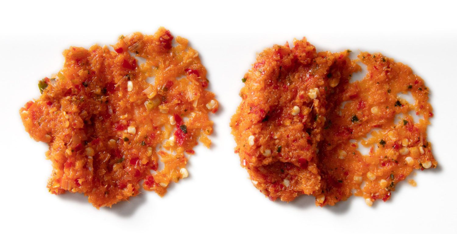 Two samples of Thai curry paste spread side-by-side on a white plate. At left, the All-Clad chopped up the tough ingredients, but longer stands of fiber remain along with seeds. At right, the Breville fully minced everything, with only the pepper seeds escaping its blades.
