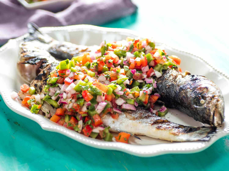 Grilled whole fish with molho à campanha (Brazilian pico de gallo) spooned over it