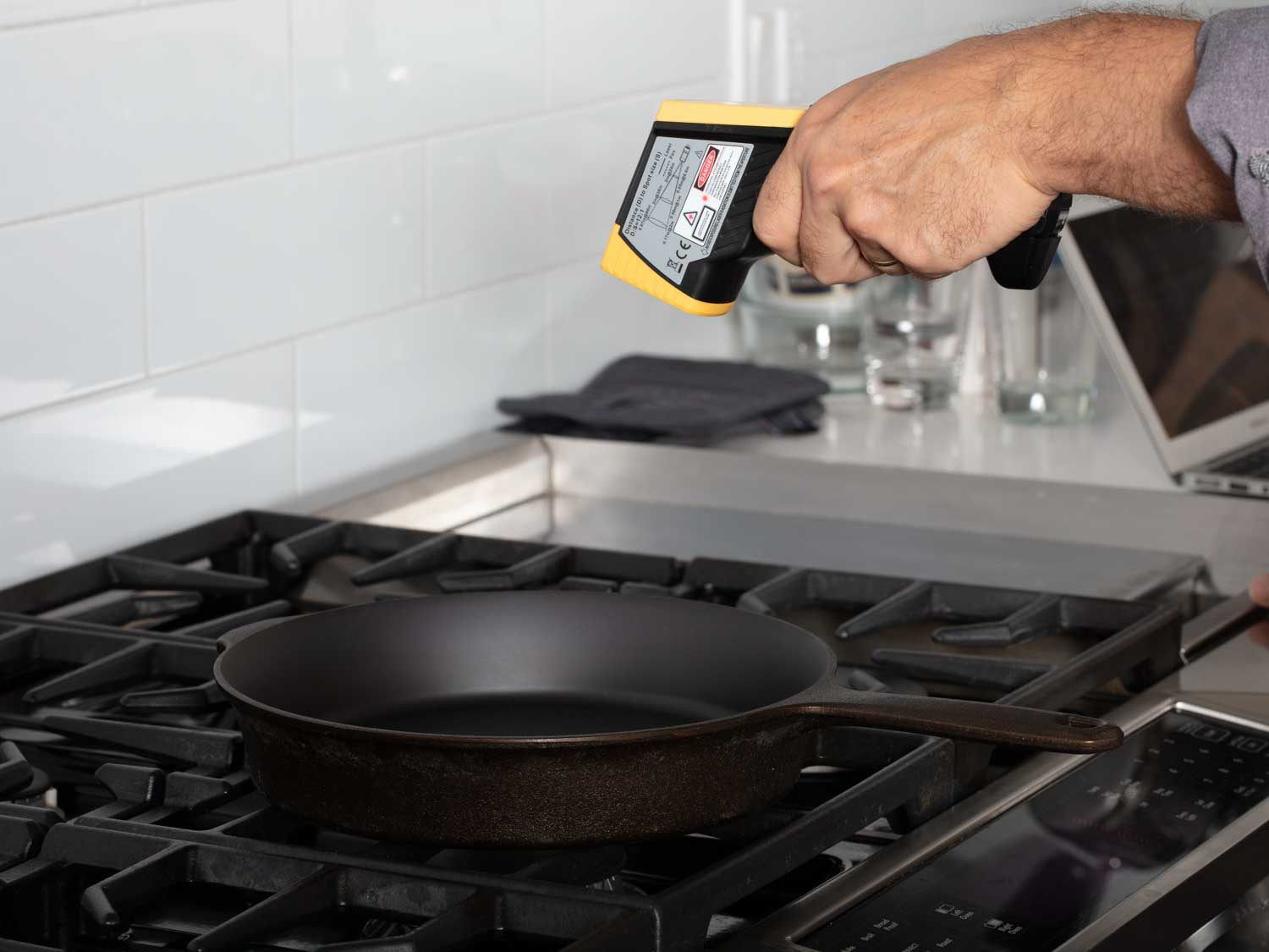 The reviewer uses an infrared thermometer to measure heat on the surface of a cast iron skillet over a moderate flame.