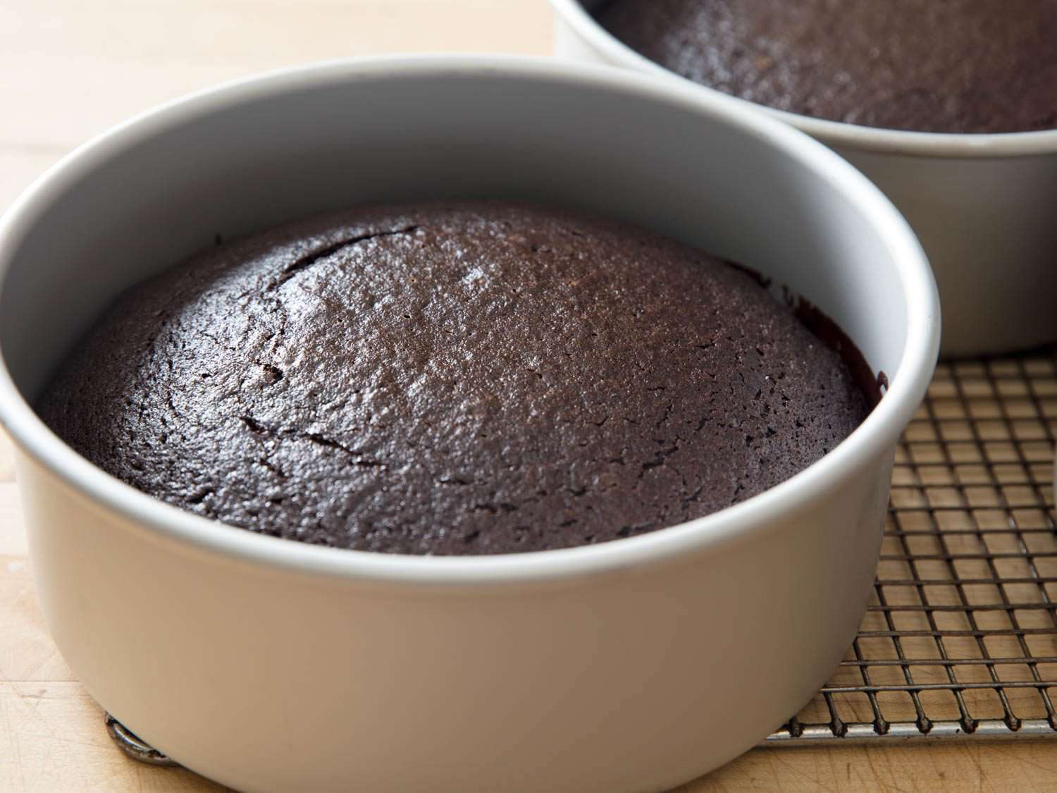 One baked layer of Devil's food cake still in cake pan on cooling rack, with second layer behind it.