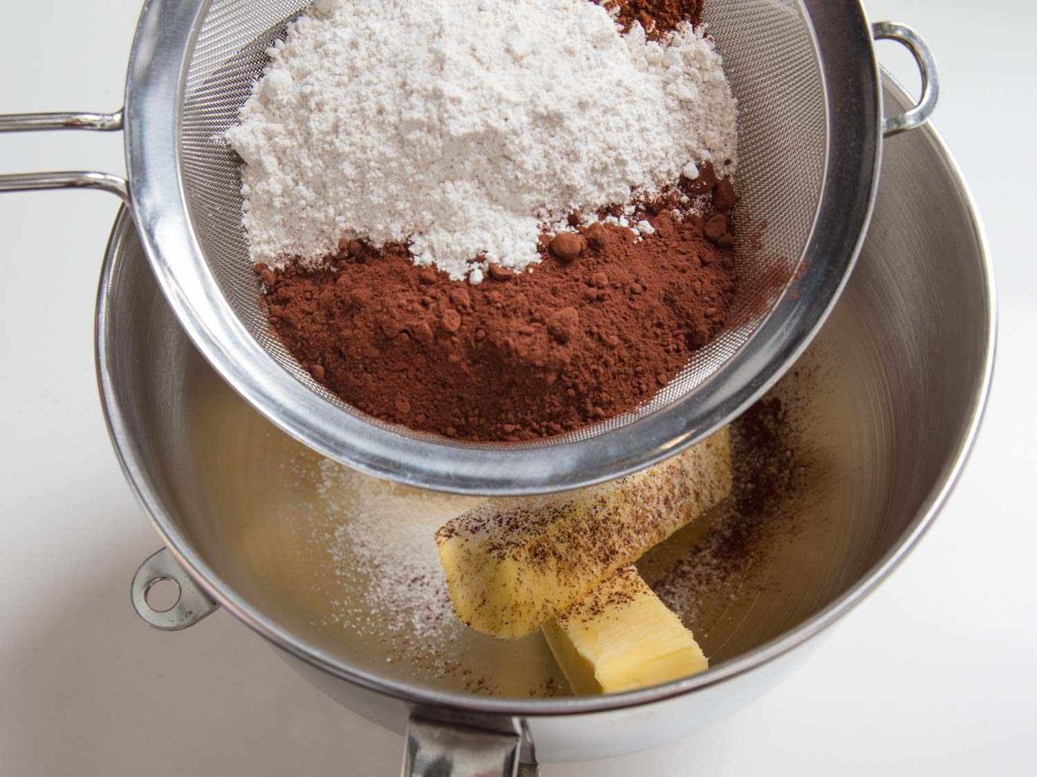 sifting cocoa and powdered sugar over butter