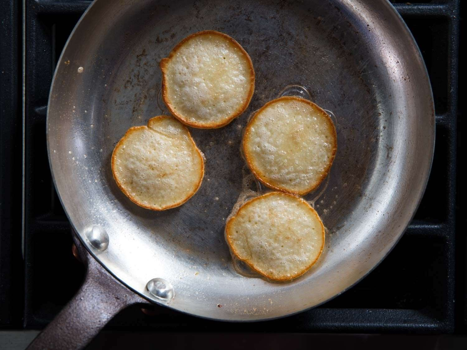 Blini cooking in a copper skillet, showing even browning