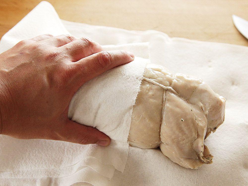 patting dry turkey porchetta with paper towel