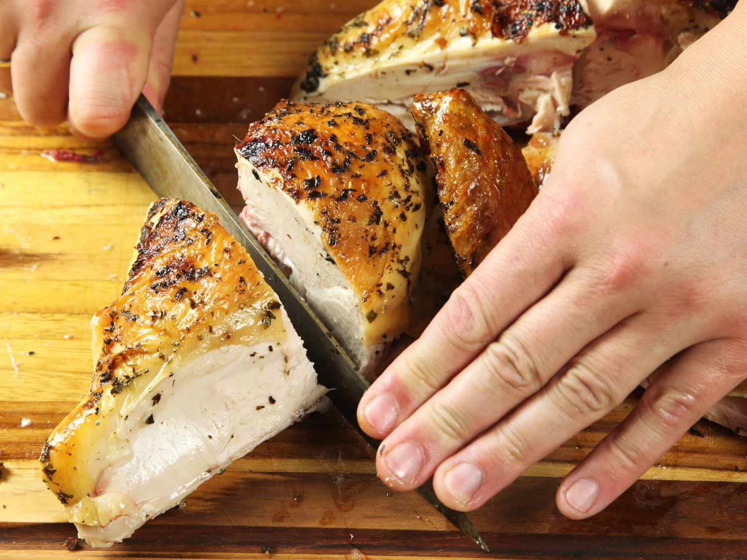 Cutting a chicken breast in half while carving a spatchcocked roast chicken.