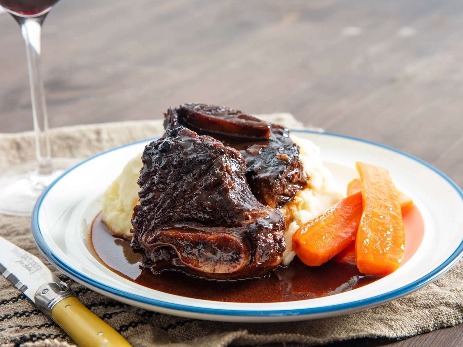 Red-wine braised beef short ribs on a plate with the rich, reduced sauce and sides of mashed potatoes and carrots