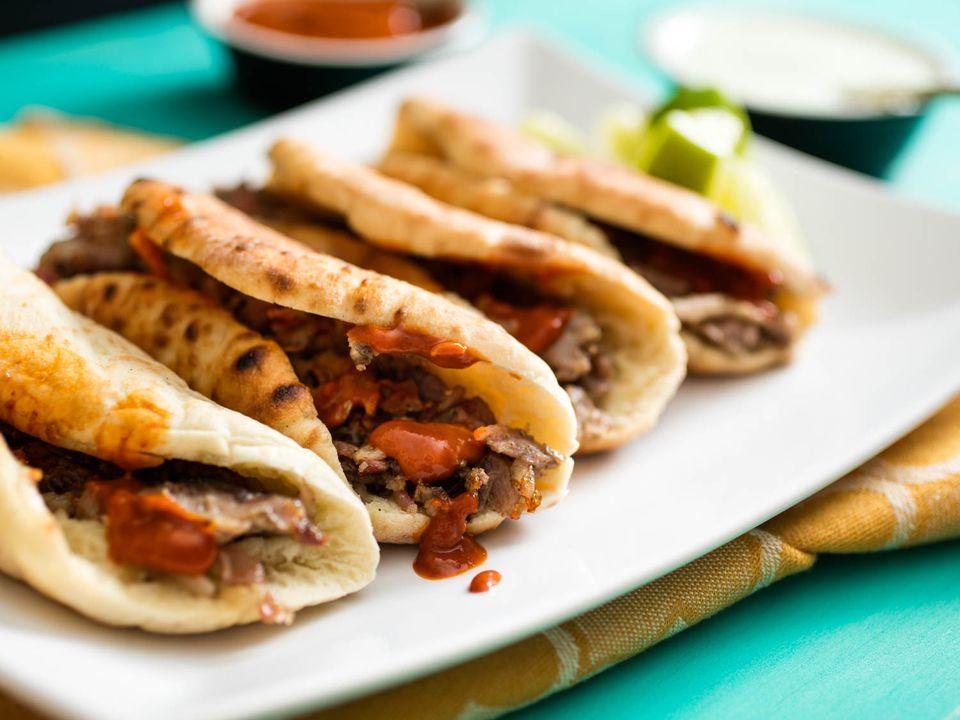 A plate with four tacos árabes.