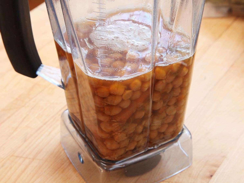 A blender jar full of chickpeas and liquid.