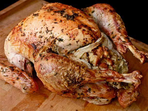 Closeup of whole roast turkey with exposed stuffing in cheesecloth pouch