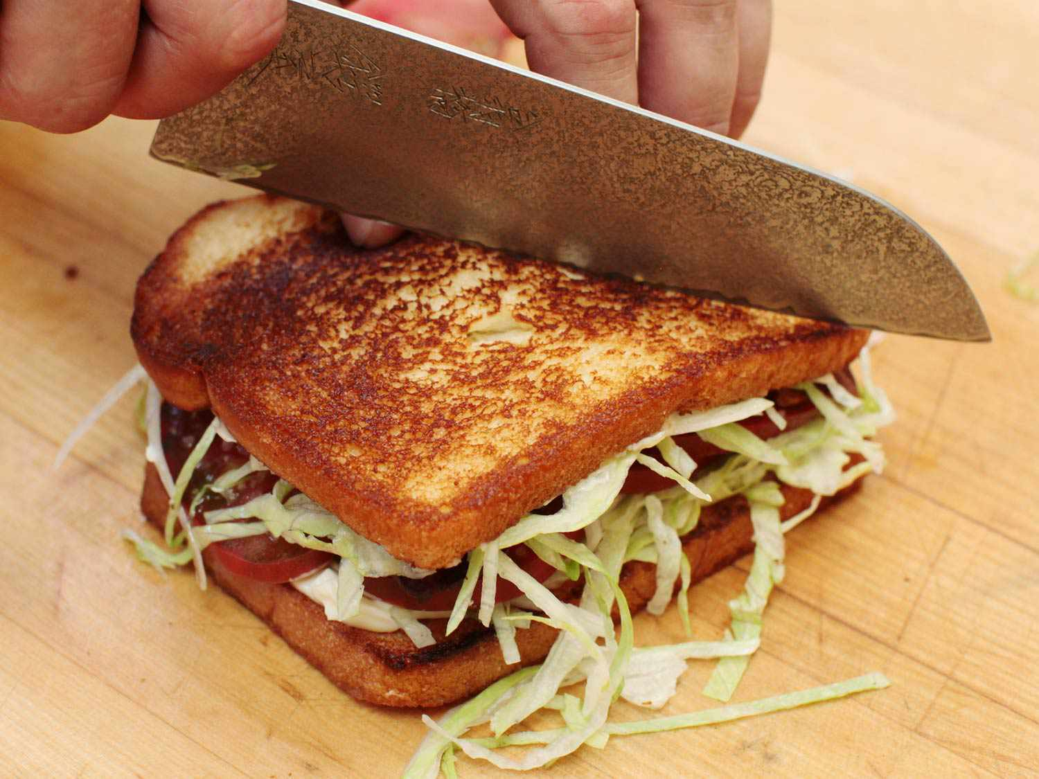 A chef's knife slicing a finished BLT sandwich in half