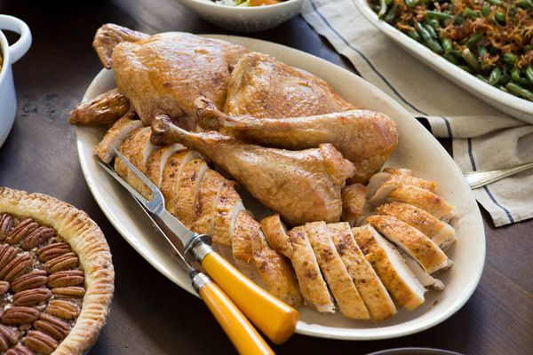 A platter of carved turkey with a carving knife and fork, surrounded by pecan pie, green bean casserole, and salad