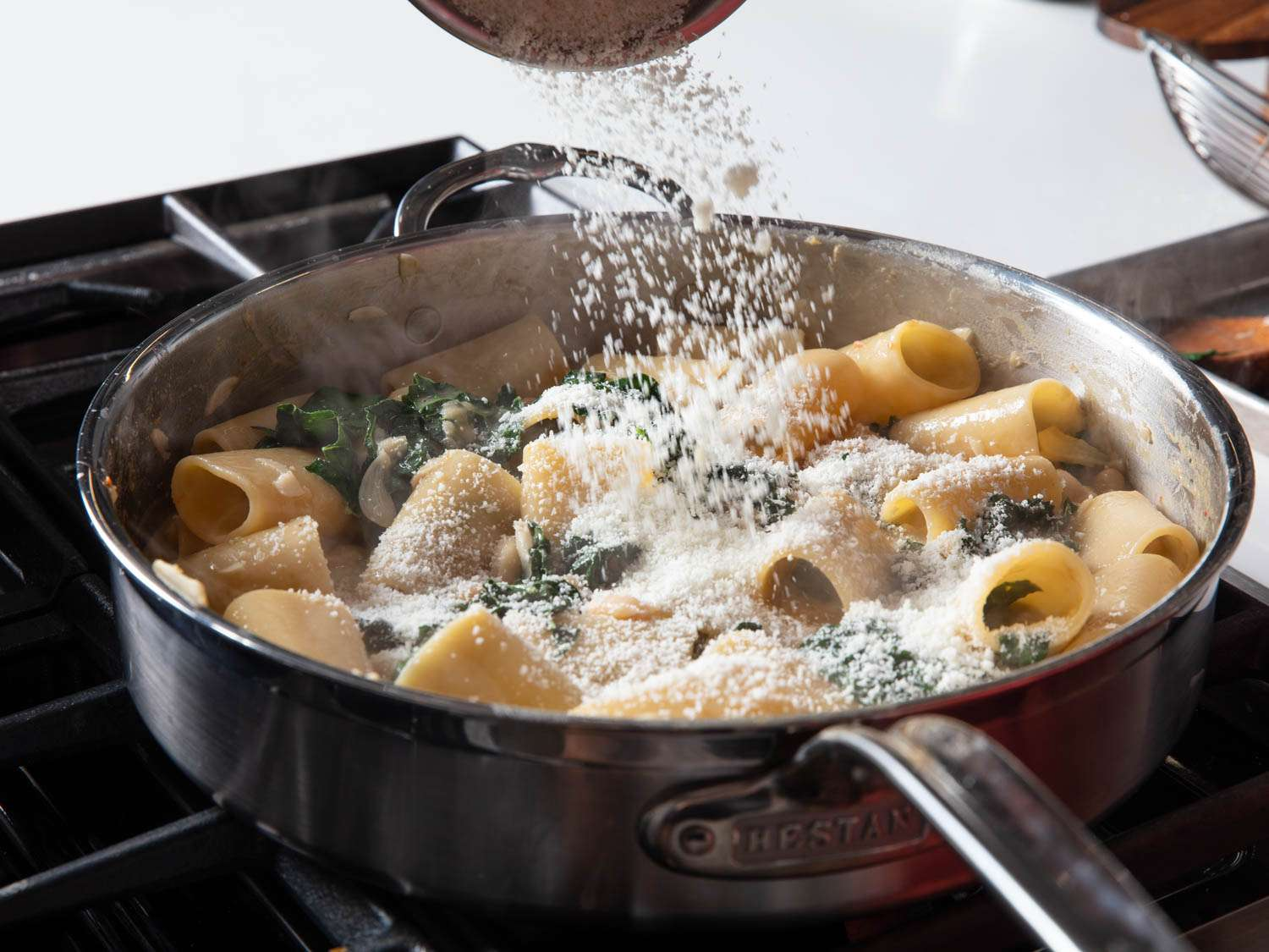 Adding cheese to a pan of rigatoni with bean sauce