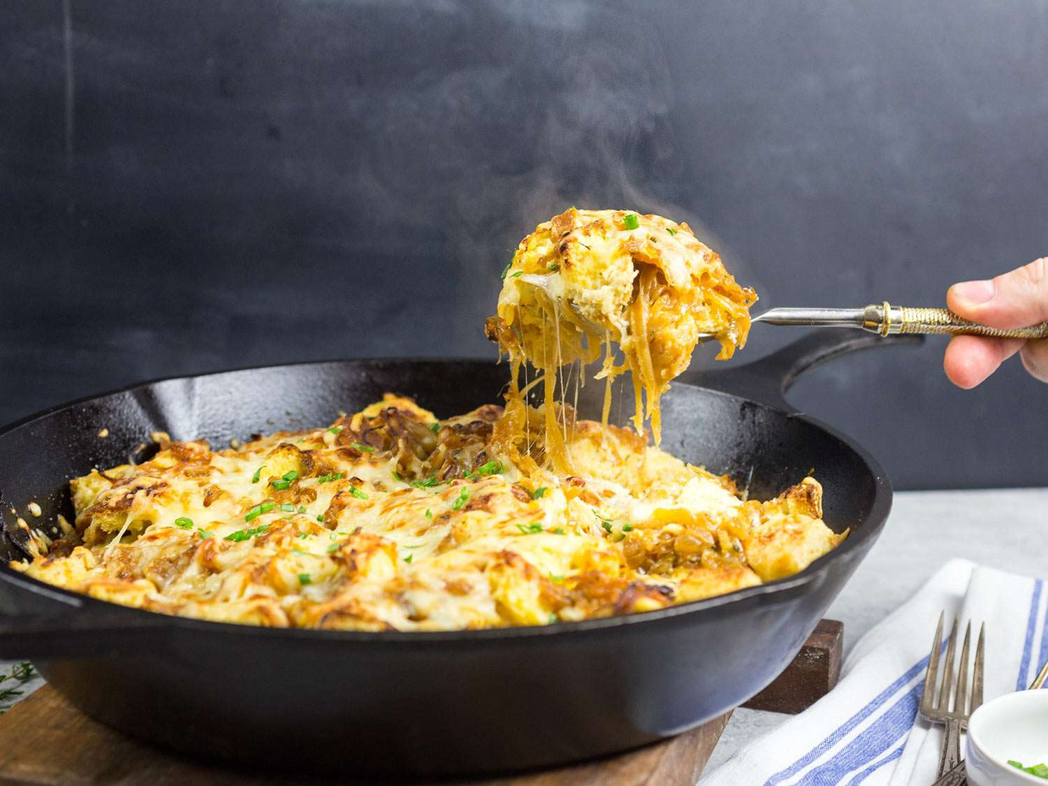 French Onion Strata in a skillet with a spoon of cheesy strata held above the skillet.