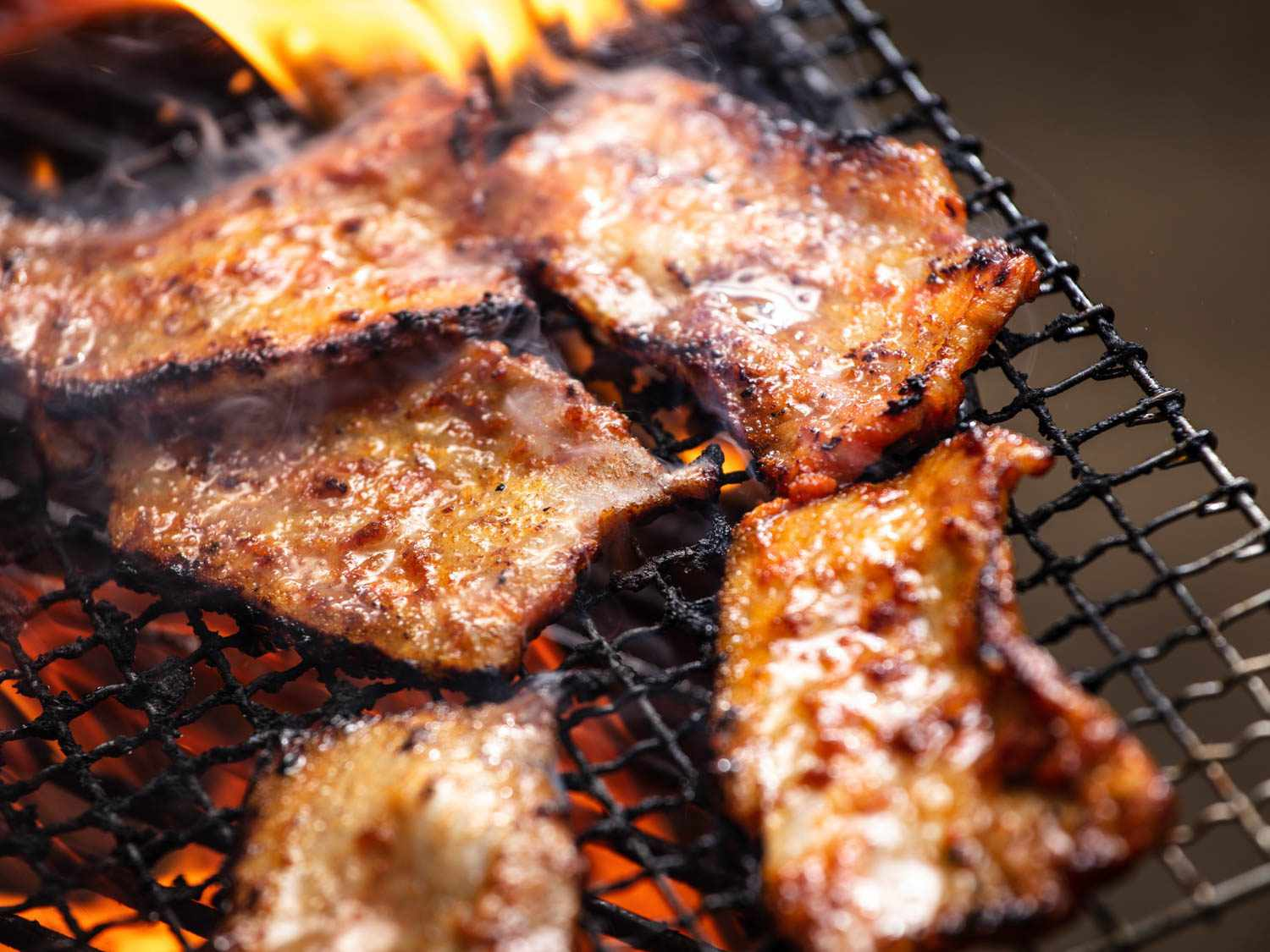 Pieces of pork belly sizzling on the grill.
