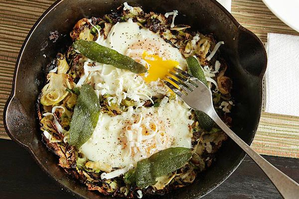 Brussels Sprouts Hash With Fried Sage and Soft Cooked Eggs in a cast iron skillet.