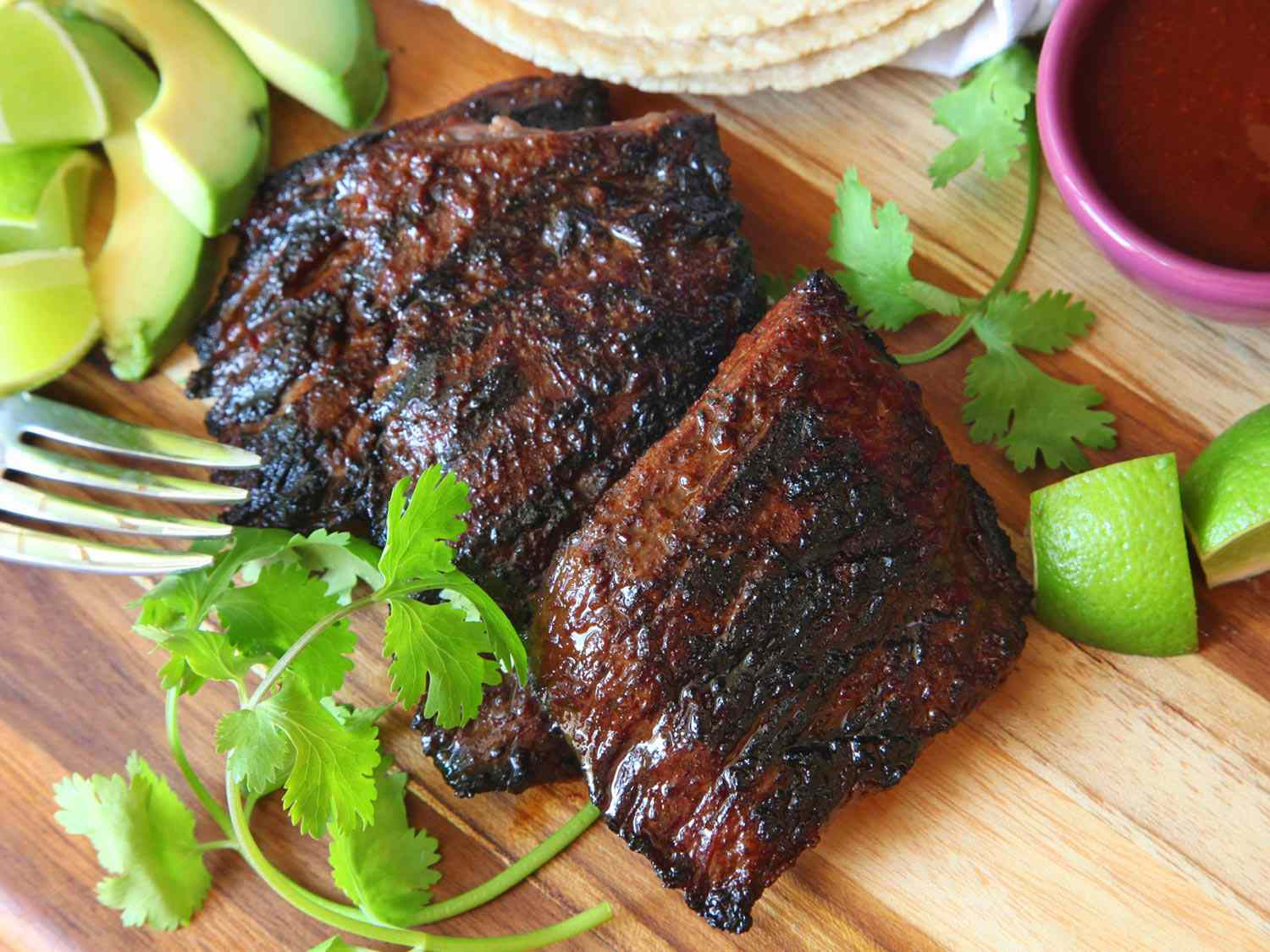 Whole grilled carne asada on a wooden cutting board with garnishes before being sliced.