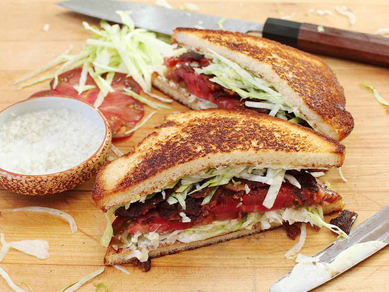 Diagonally cut BLT sandwich halves, next to a small bowl of coarse salt, sliced tomato, and shredded lettuce