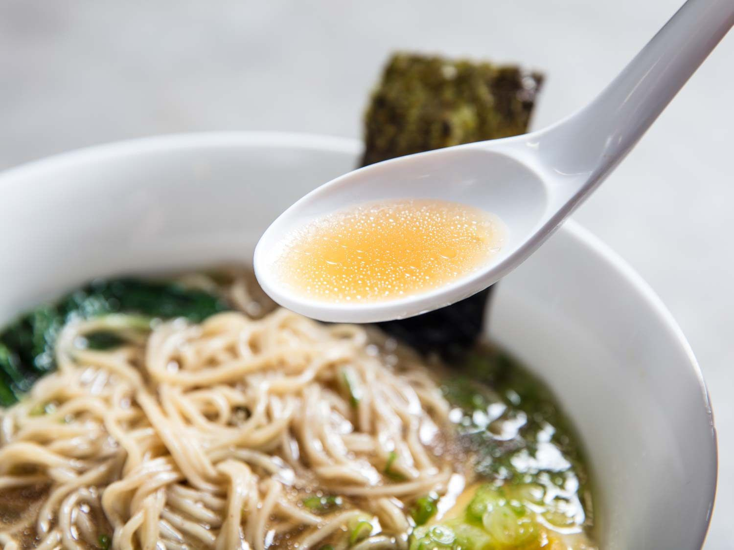 A spoonful of shoyu ramen broth being lifted from a bowl of broth and noodles