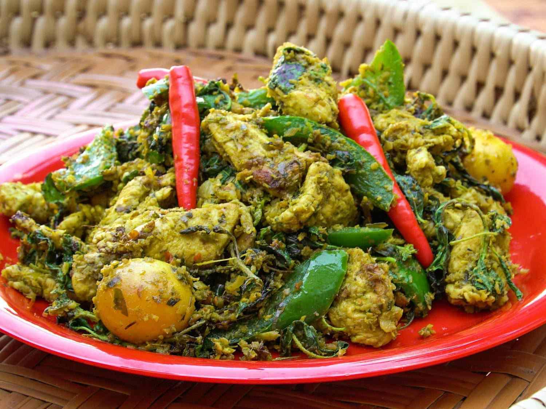 Cha kreung satch moan (Cambodian chicken stir-fry) on a red plate