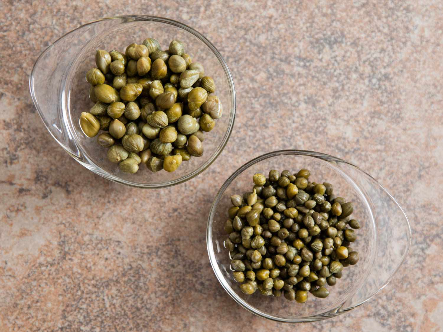 Two small bowls of different sized capers.