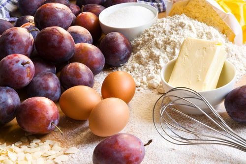 A pile of plums with whole brown eggs, a pile of flour, a small bowl of sugar, a whisk, and a bowl with a half pound of butter on a counter.