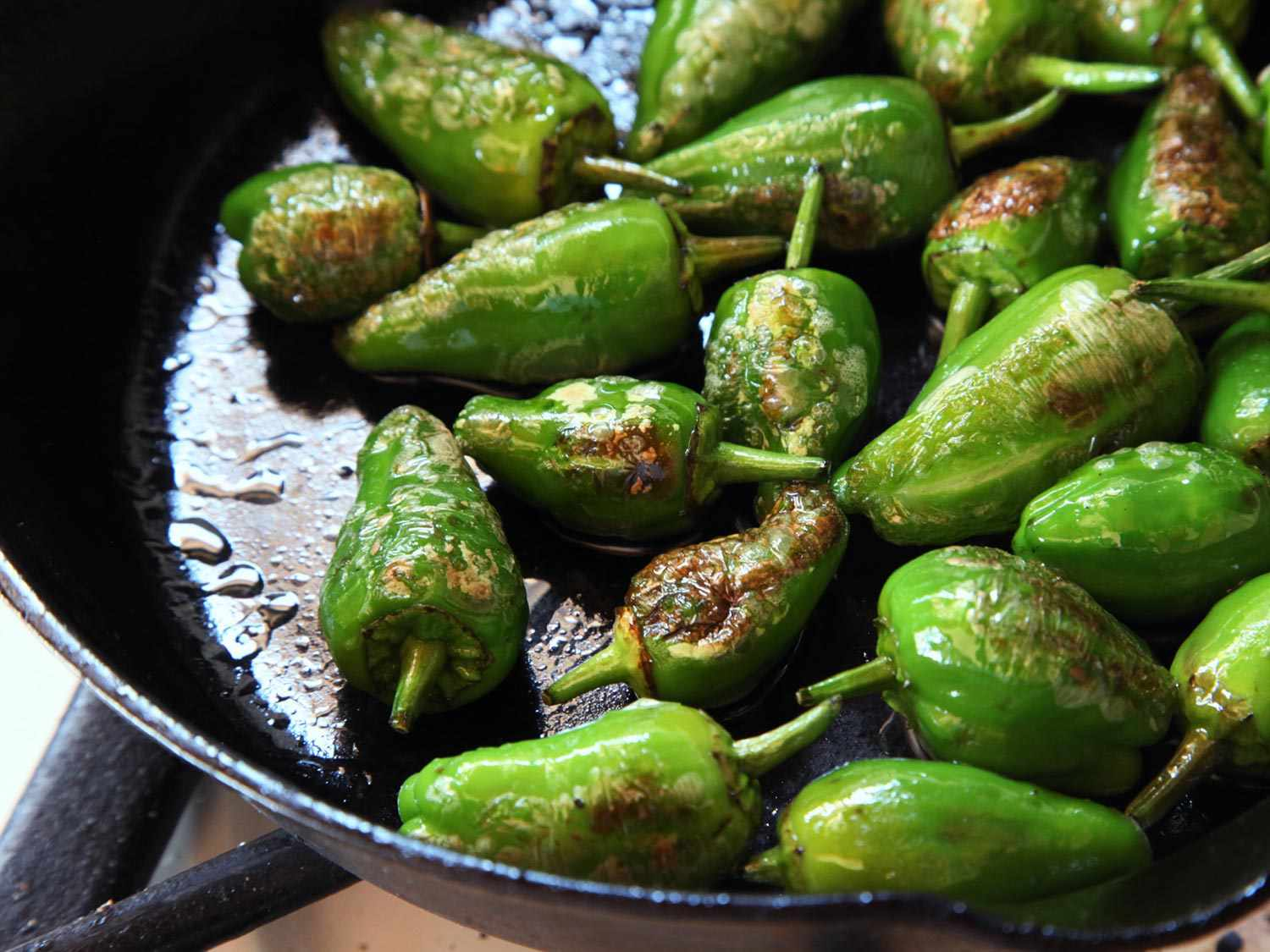 Spanish-style Padrón peppers in a cast iron skillet; some are charred and blistered.