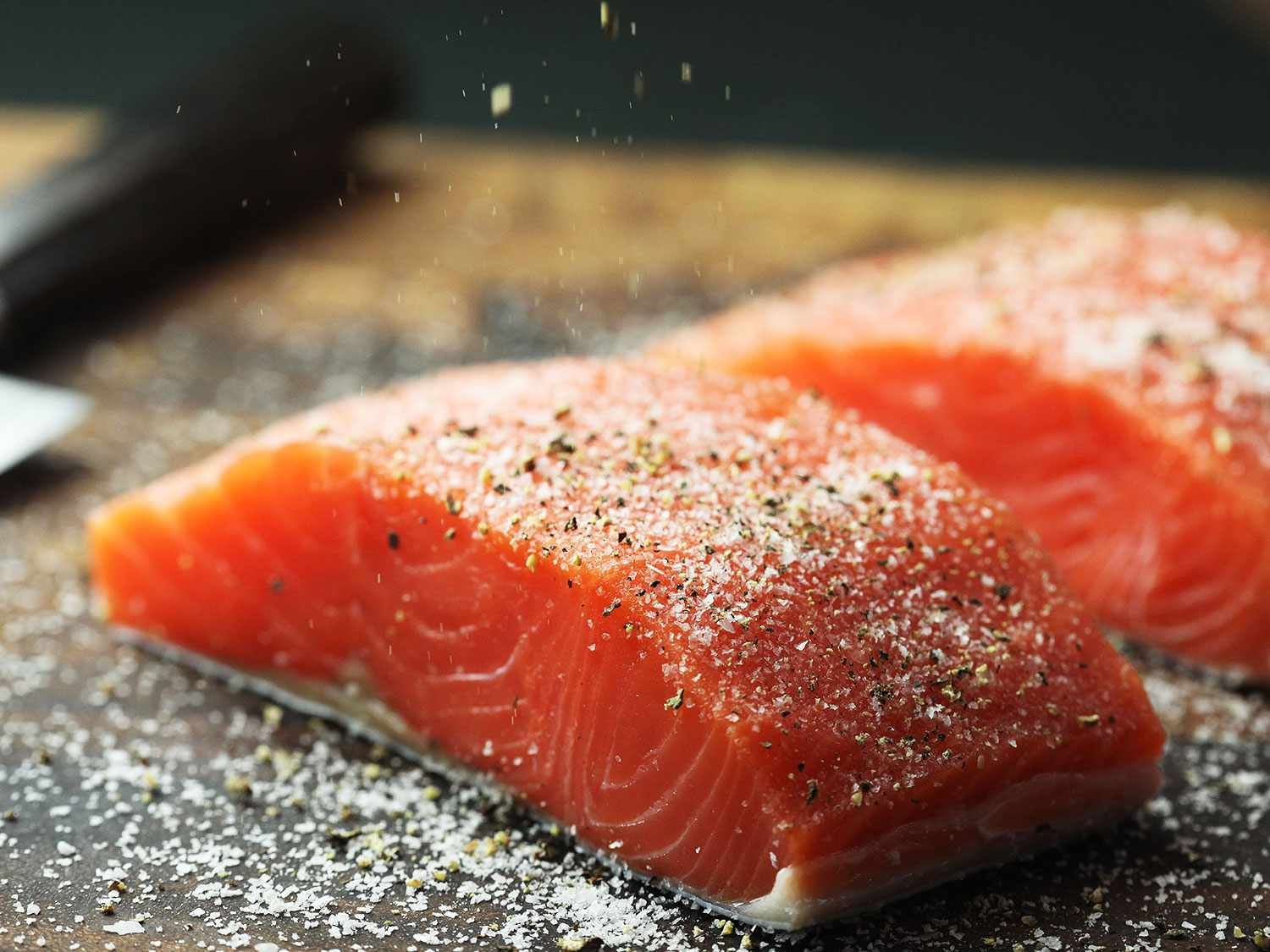 Seasoning two skin-on salmon fillets with salt and pepper on wooden cutting board.