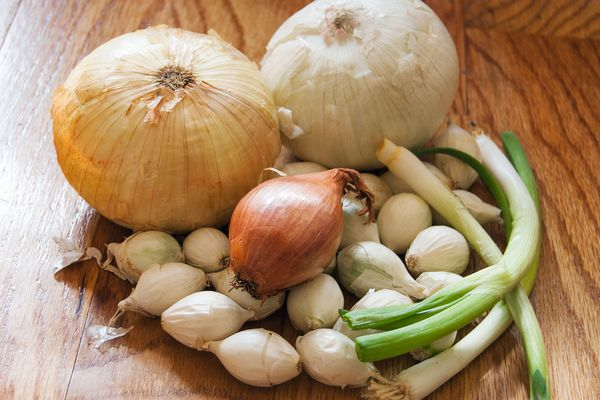 A pile of different types of whole, unpeeled onions on a cutting board.