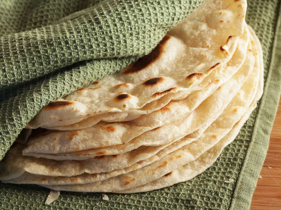 A stack of cook-and-serve flour tortillas wrapped in a green kitchen towel.