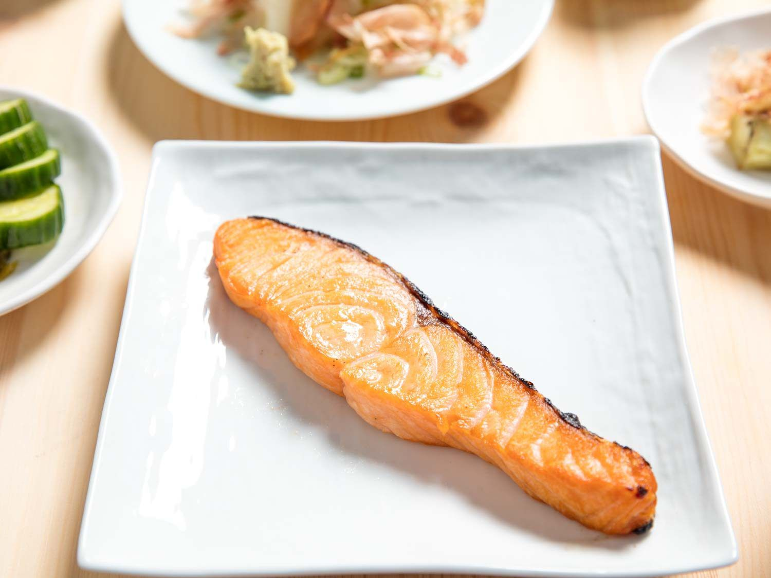 A piece of broiled salted salmon on a white plate