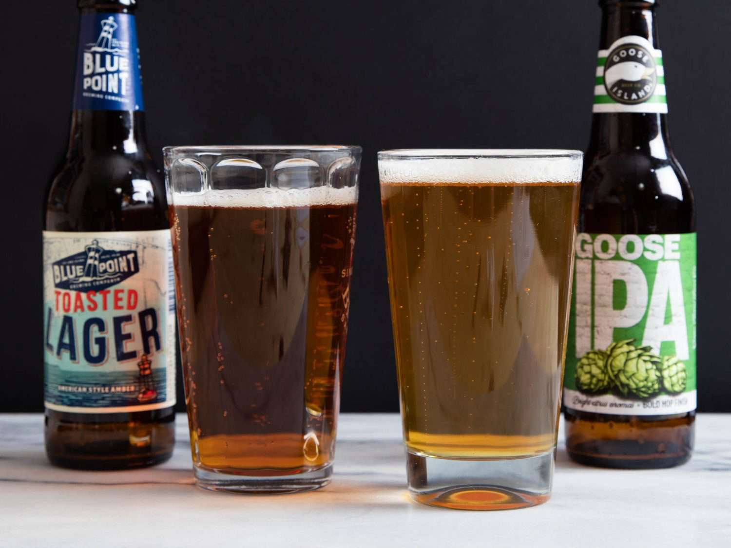 A lager and an IPA, each poured in glasses with the bottles next to the beer.