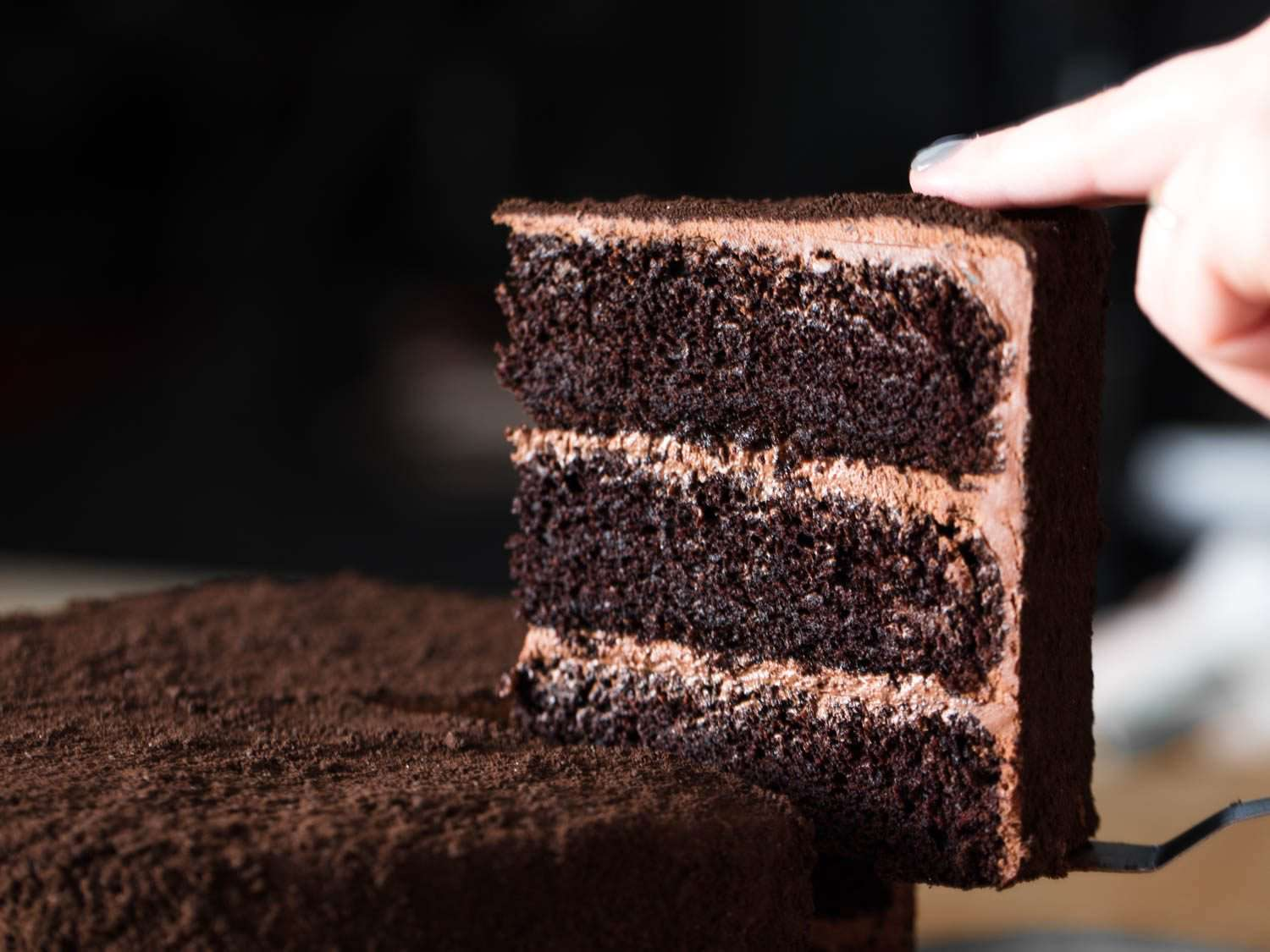 Pulling out a slice of three-layer chocolate Devil's food cake.