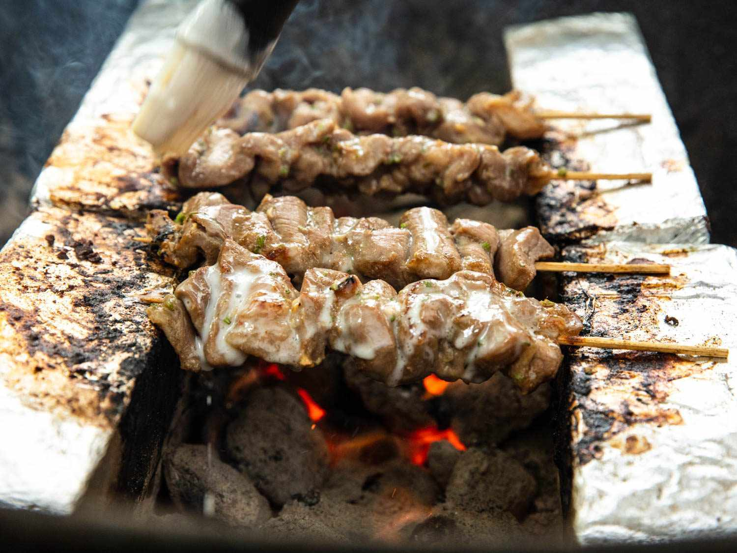 Several Thai pork skewers cooking over charcoal, suspended between two parallel rows of foil-wrapped bricks