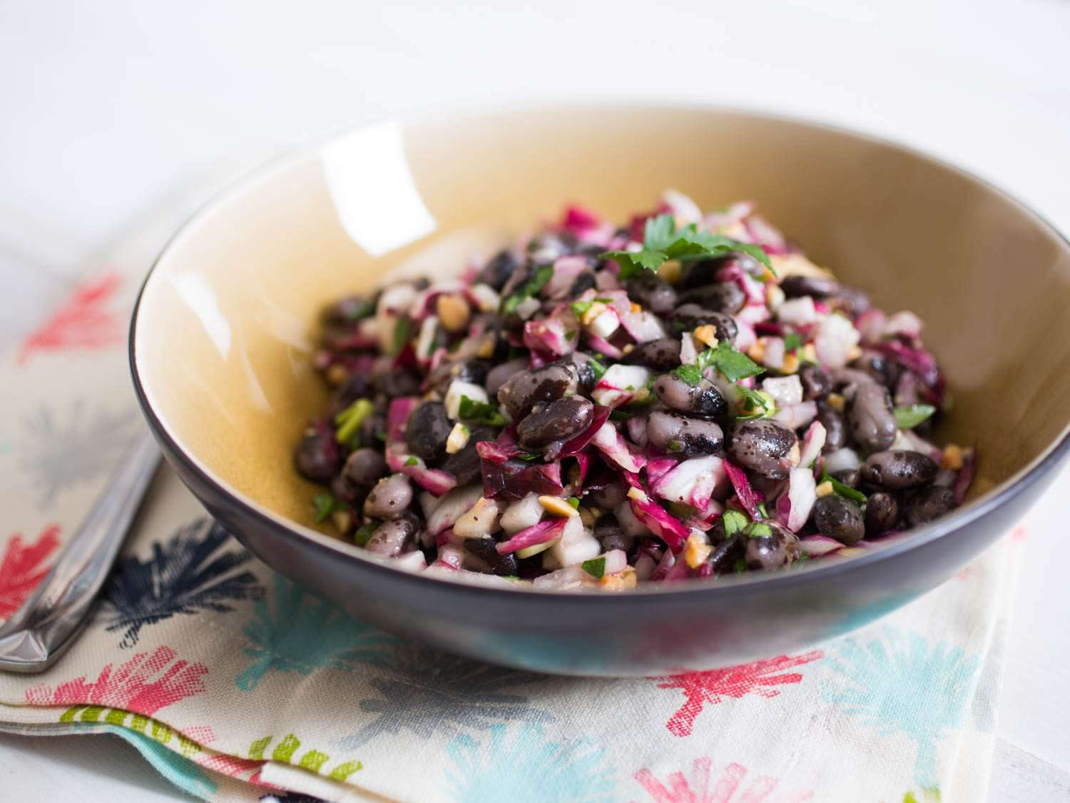 A ceramic bowl of Bean Salad With Radicchio, Radish, Pickled Onions, and Marcona Almonds