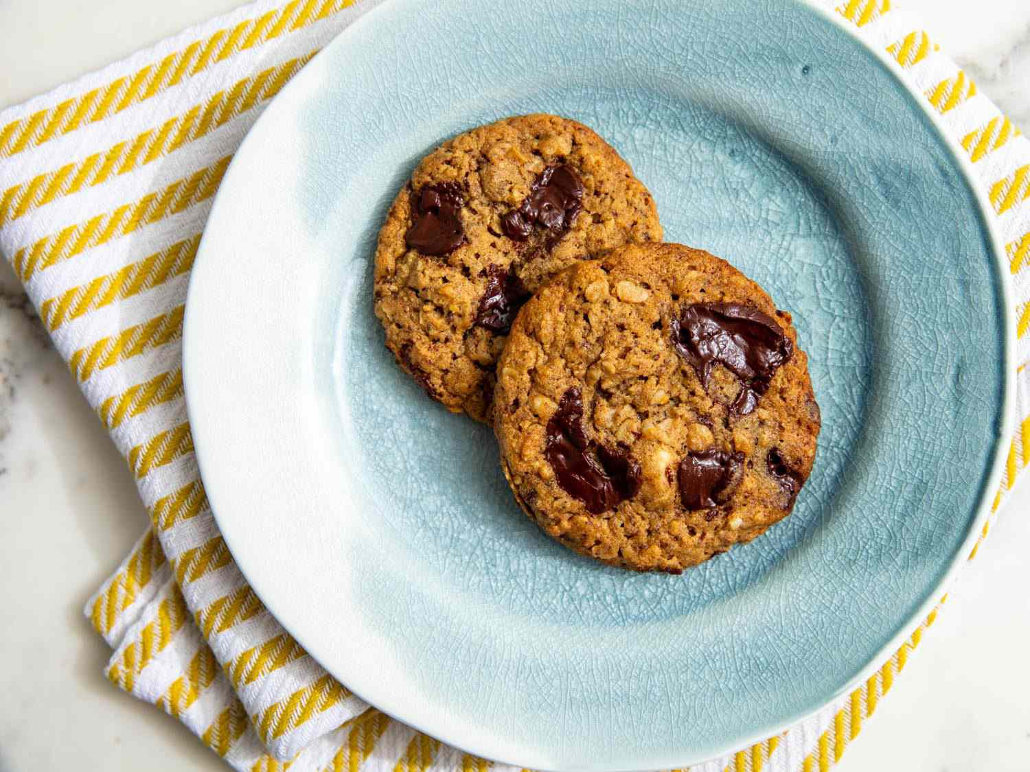 two oatmeal chocolate chip cookies on a blue plate, seen from above