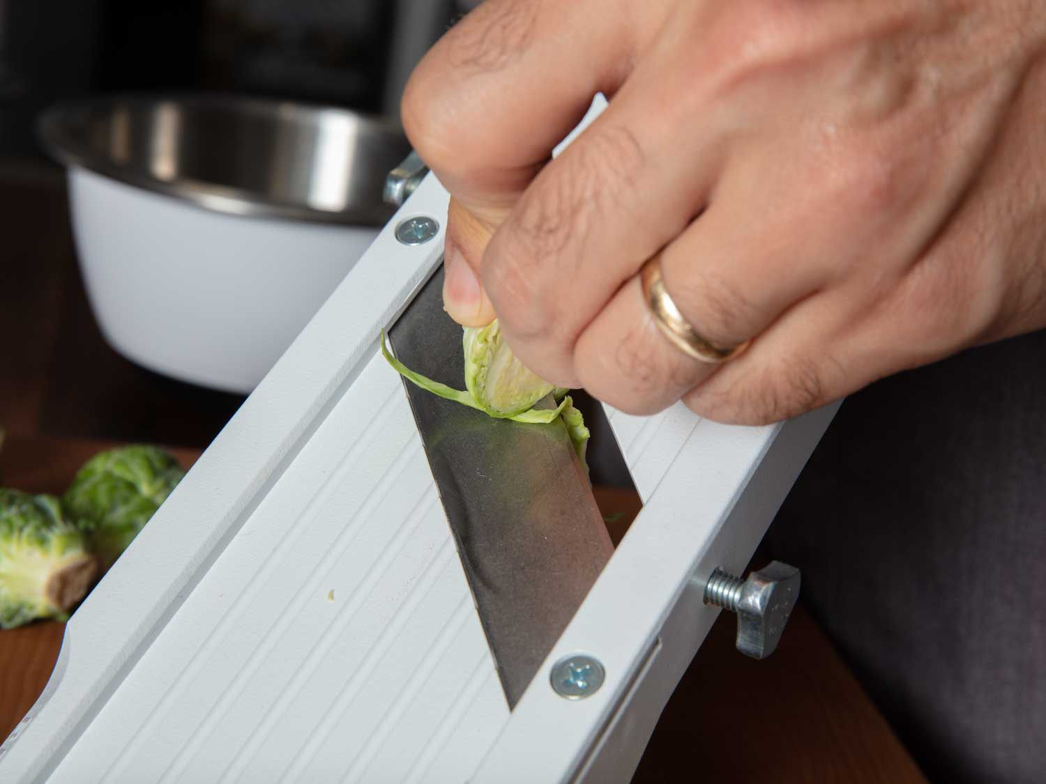 Thinly slicing Brussels sprouts on a mandoline slicer